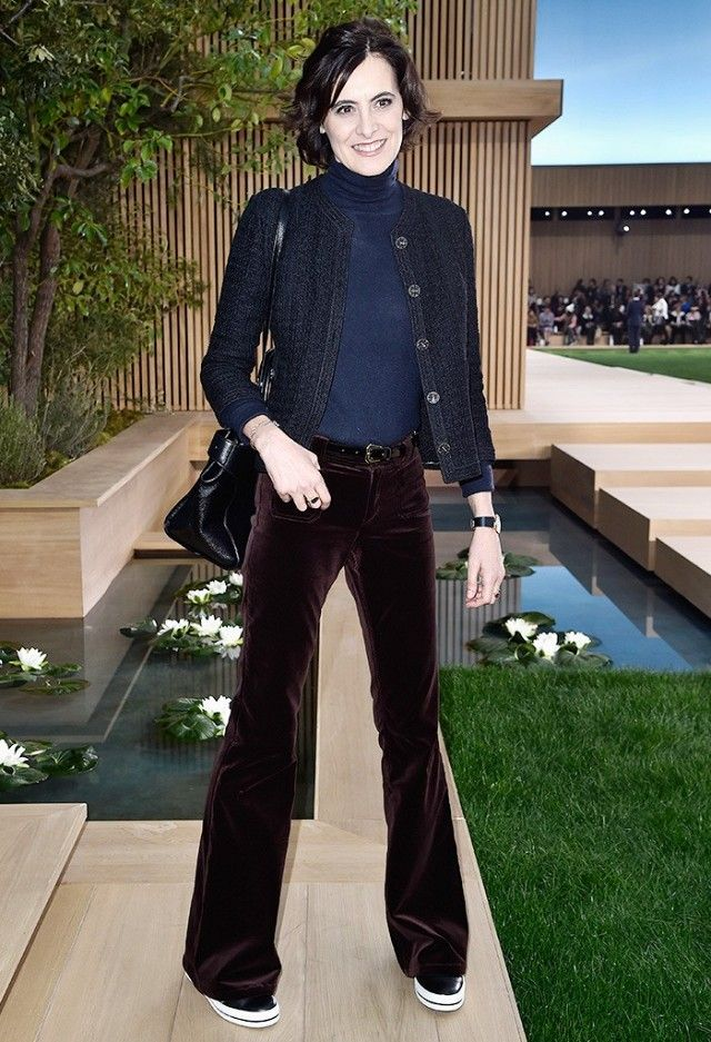 Inès de la Fressange wears a navy blue turtleneck, tweed Chanel jacket, belted velvet flares, and platform sneakers