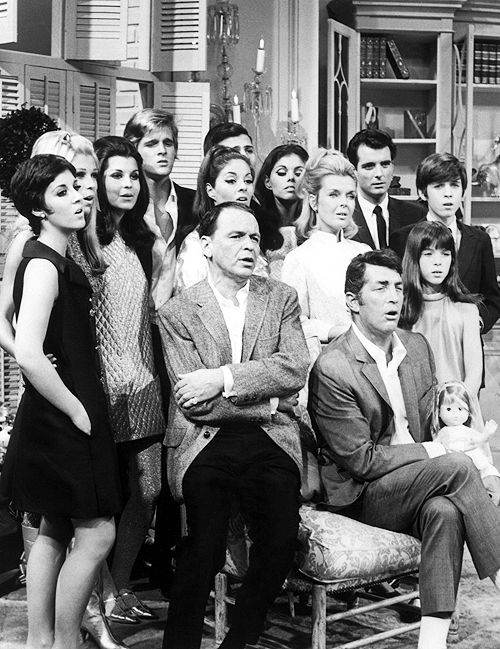 The families of Dean Martin and Frank Sinatra sing Christmas carols on Martin's 1967 Christmas special. L to R: Deana Martin, Nancy Sinatra, Tina Sinatra, Dean Paul Martin, Gail Martin, Frank Sinatra Jr., Claudia Martin, Jeanne Martin, Craig Martin, Gina Martin, Ricci Martin.