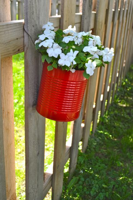 Decorate your fence with flower pots......These flower pots (made with tin cans) are a great way to reuse and recycle. I think it would also be fun with smaller sized cans, too.  Spray paint the cans with your favorite fun colors, add wire around them to hang on a fence, & fill them with soil & flowers. These cans will probably generate a lot of heat, so make sure to use heat tolerant plants so you can enjoy them all summer long. You may want to poke some holes in the bottom for drainage…