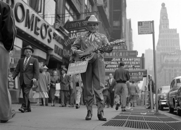 Man dressed as a cowboy playing guitar to promote the film Johnny Guitar, NYC