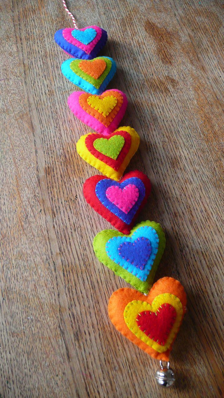 Colorido fieltro corazones colgador de la pared / por HetBovenhuis