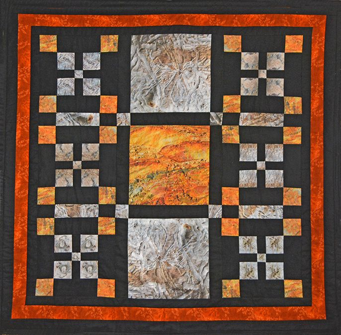 This wallhanging has photos of tree bark and colourful clay with black background.