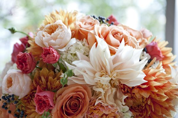 Close up of peach and orange floral by Fiore Blossoms with navy privet berries. Juliet garden roses, Cinnamon and Finesse roses, Cafe au lait pale peach dahlias, dark orange dinner plate dahlias and pink spray roses.