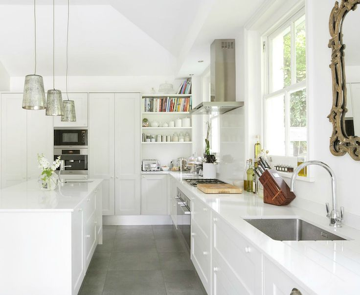 Modern European kitchen with white kitchen cabinets, white kitchen island, white quartz counter top, gold ornate mirror, polished chrome gooseneck faucet, mercury glass pendants, gray slate tiles floor and white built-ins.