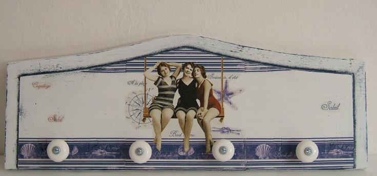 Věšák A la plage Tento retro věšák je vyroben technikou decoupage a patinování. S motivem tří žen v plavkách na houpačce. Doplněn čtyřmi stylovými porcelánovými knopkami. Toto zboží je vyrobeno tak, aby vypadalo starobyle. Trhlinky, šmouhy či patina nejsou vadou. Materiál: dřevo, akrylová barva, lak. Úchytky: porcelán, ocel. Barva: tmavě modrá v kombinaci s bílým ...
