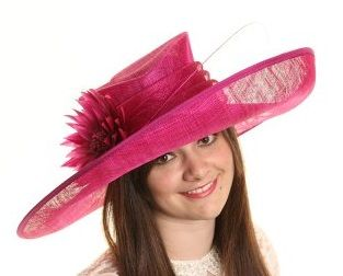 The large statement styled brim is 21 inches in diameter at longest side and edged in a satin effect trim and has a great turn up at one end The topper is quite different in that it is slightly tear drop shaped with a flat top which has a present moon bevel created within it The large layered band supports a pretty satin effect material flower