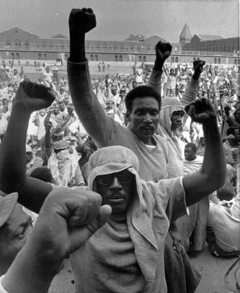 Inmates of Attica state prison in upstate New York raise their fists to show solidarity in their demands during a negotiation session with state prisons Commissioner Russell Oswald Sept. 10 1971 during the Attica prison riot. [492x600]