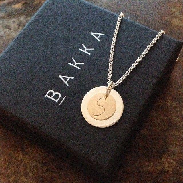 Initialsmykke i gull med et skjult hjerte i sølvplaten under