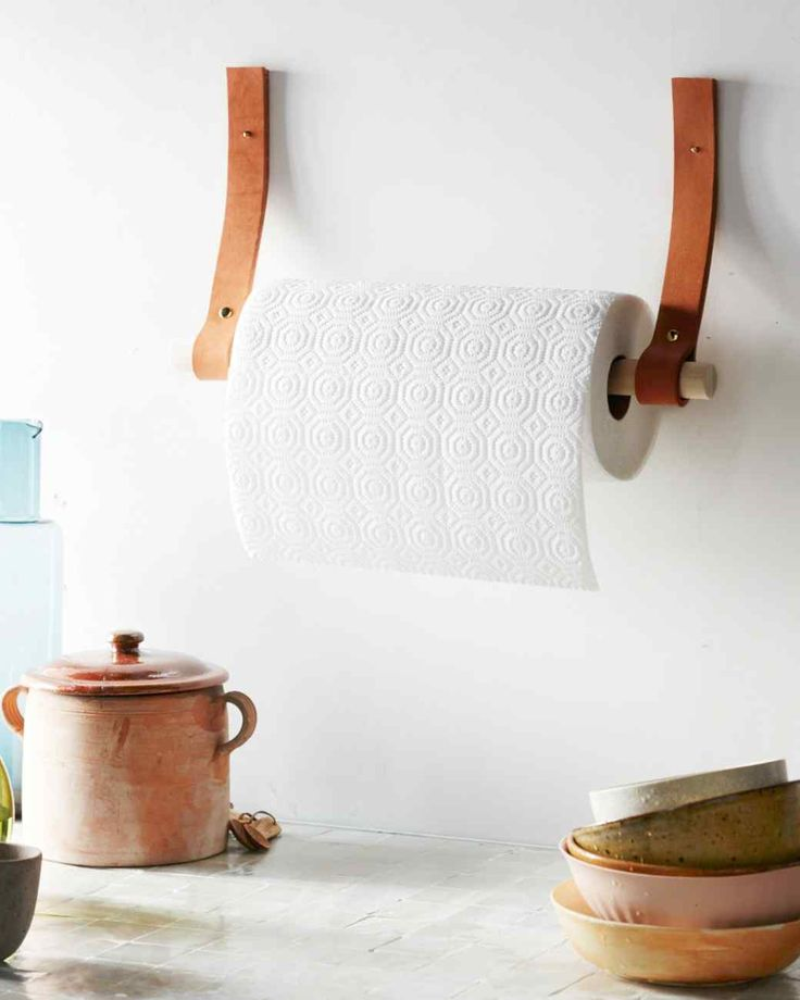 Here's a stylish solution for keeping paper towels handy. All you need to hang the roll from the wall are riveted straps of leather and a wooden dowel.