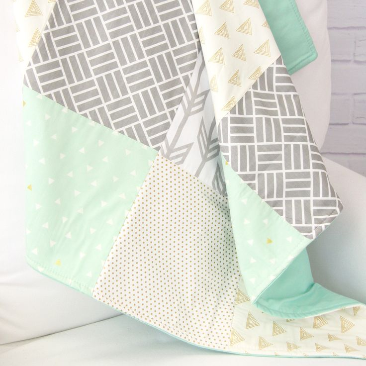 This modern baby quilt comes in a soft and neutral mix of gray, mint, and gold prints with various triangle, line, and arrow patterns. Our Mason's Mint & Gold Arrow Baby Quilt is the perfect baby show