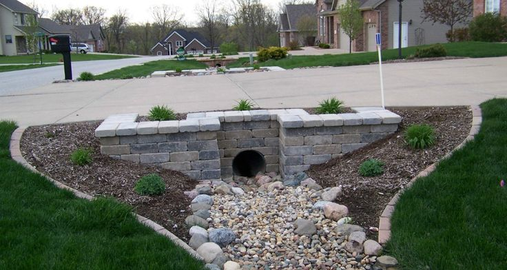 Reatiningwall driveway beautification landscaping for Drain pipe landscaping