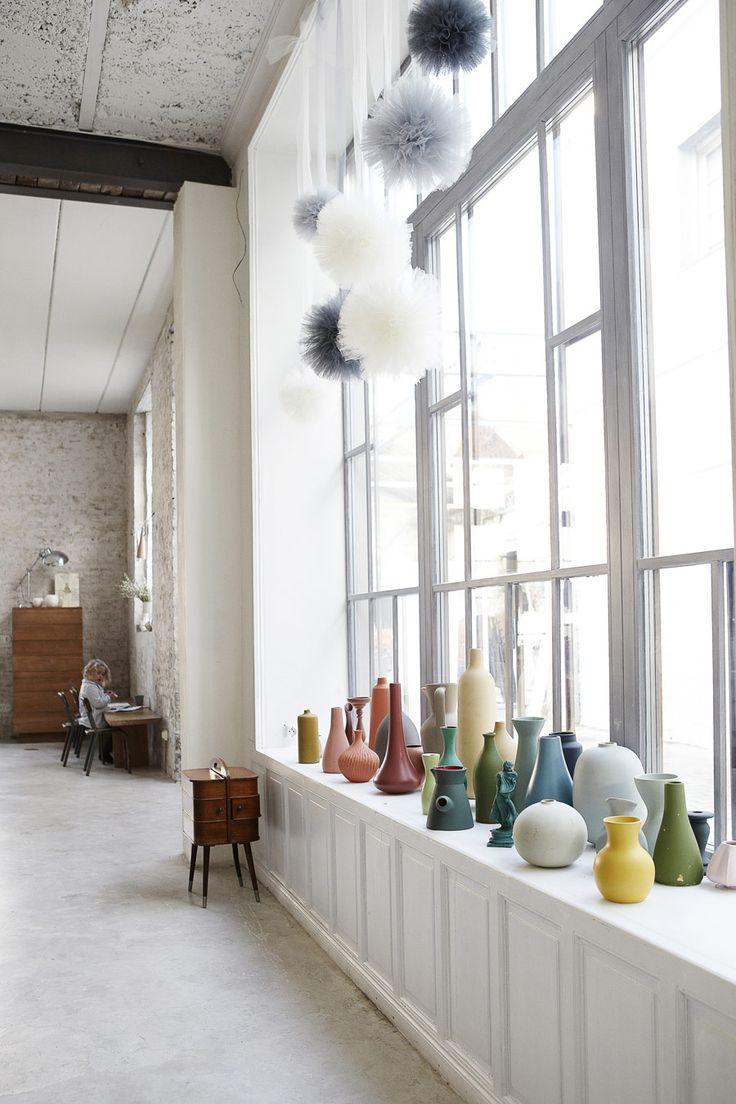 Dans une vaste pièce d'ancienne usine, la blancheur minimaliste de la déco est contrebalancée par la collection de céramiques de toutes les couleurs.