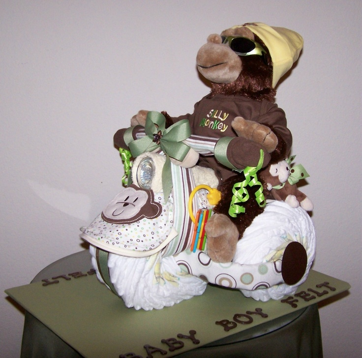 """DIAPER TRICYCLE I made.  I used 18 diapers for each back tire and 26 for the front tire.  I used one 12"""" plush monkey, a onesie that says, """"Silly Monkey.""""  I also used 4 receiving blankets, 4 bibs, 2 washcloths, bottle, baby socks on handle bars, toy keys to start the engine with (lol), baby hat, stylish baby sunglasses, small toy monkey and on the other side his shoes hanging from the fender.  These are my best selling shower centerpiece."""