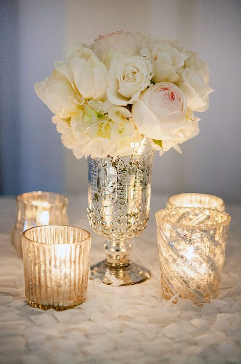 Four mercury votives surround a silver vase packed with romantic roses and hydrangea over a floral textured tablecloth. #WeddingFlowers #Candles #Wedding Decoration