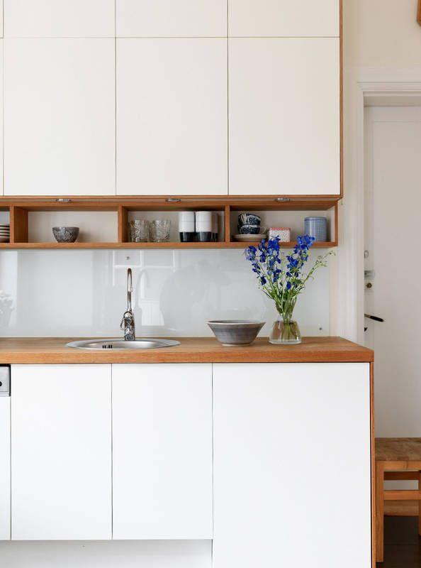 Prostą białą zabudowę kuchni ocieplają drewniane półki, boki mebli i blat. Ścianę między górnymi a dolnymi szafkami osłonięto panelem z mlecznego szkła, który jest dyskretnym elementem wystroju. Jego połyskliwa powierzchnia tworzy ciekawy wizualnie efekt.