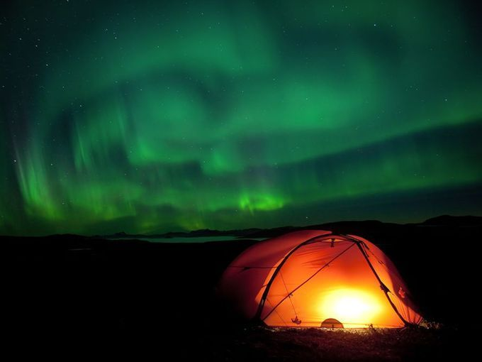 Aurora light displays can glow numerous colors, including green and red, and often appear as curtain-like waves in the sky