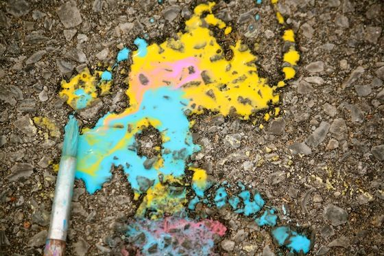 homemade yellow and blue sidewalk paint with paintbrush