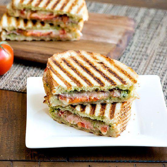 Panini with prosciutto, provolone, pesto, and tomato; all sandwiched ...