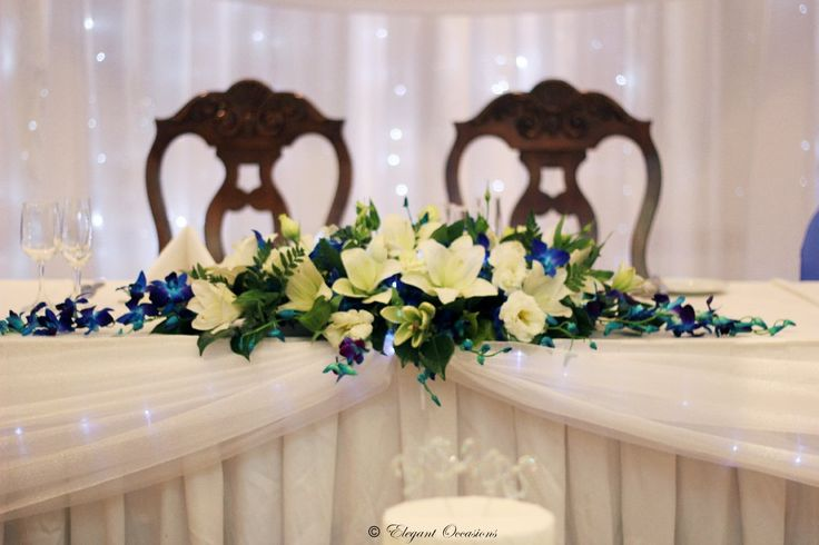 Starting from an empty room, the preparation begins for a ceiling decoration. A bridal table and ordinary round tables are then placed around the room. After the tablecloths are laid, the table settings and centrepieces can begin. The ceiling was draped with crystal white organza and long strands of fairy …