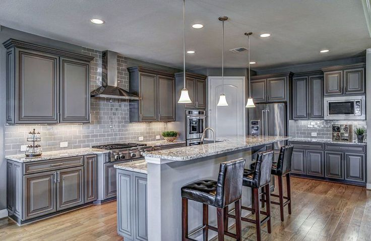 Traditional kitchen with gray cabinets and subway tile backsplash with white granite countertop and breakfast bar island