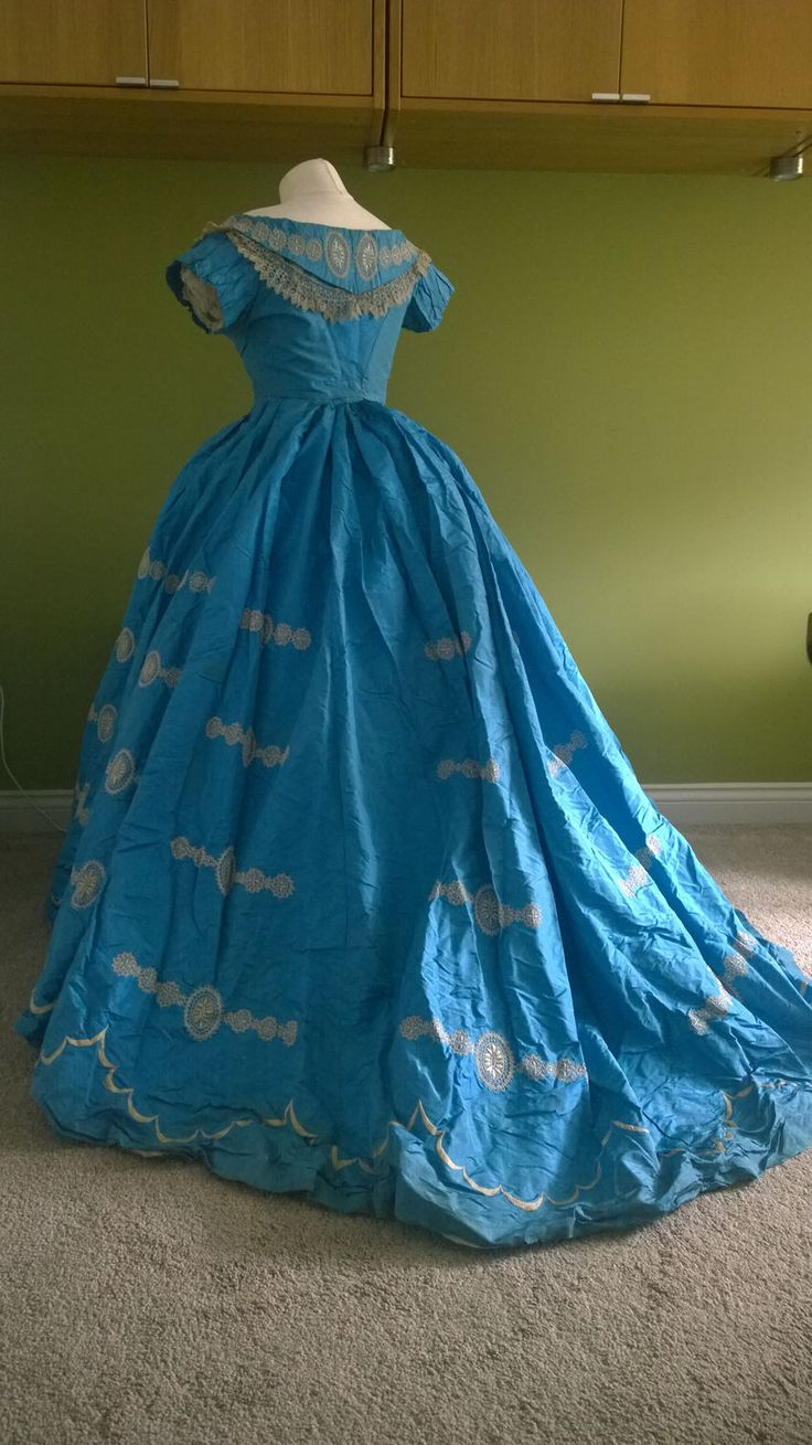 A magnificent light blue silk 1860s crinoline two piece evening gown. The skirt has a short train and is embroidered in white with classical motifs, the bodice has similar embroidery and is trimmed with lace. The colour is still fantastic , the overall impression is of a piece of Wedgewood.