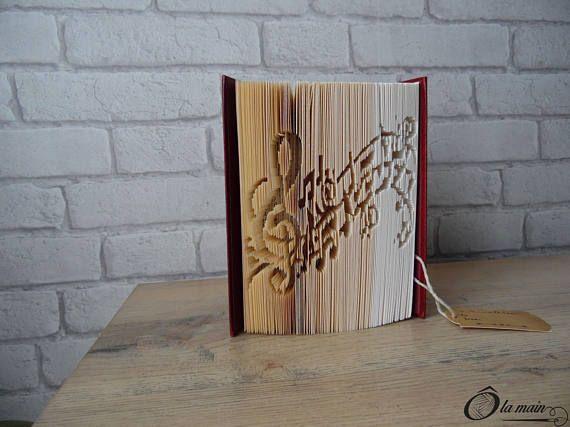 La collection A Livre Ouvert est une série de livres doccasion transformés en objets de décoration via plusieurs techniques (découpage, pliage ou décou-pliage). Chaque page est découpée et/ou pliée à la main pour donner vie à un motif.  Le modèle Musique est un livre découpé et plié pour représenter une clé de sol et une portée de notes de musique. Le livre possède une magnifique couverture bordeaux, noire et or avec le visage de Jules Verne. VENDU SEUL
