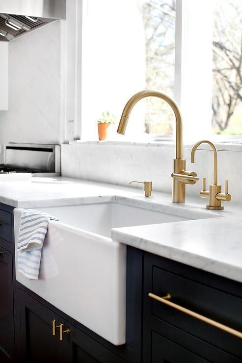 Transitional kitchen features navy blue cabinets completed with long brass pulls supporting honed white countertops fitted an undermount farmhouse sink boasting a high arc brass faucet positioned under a window.