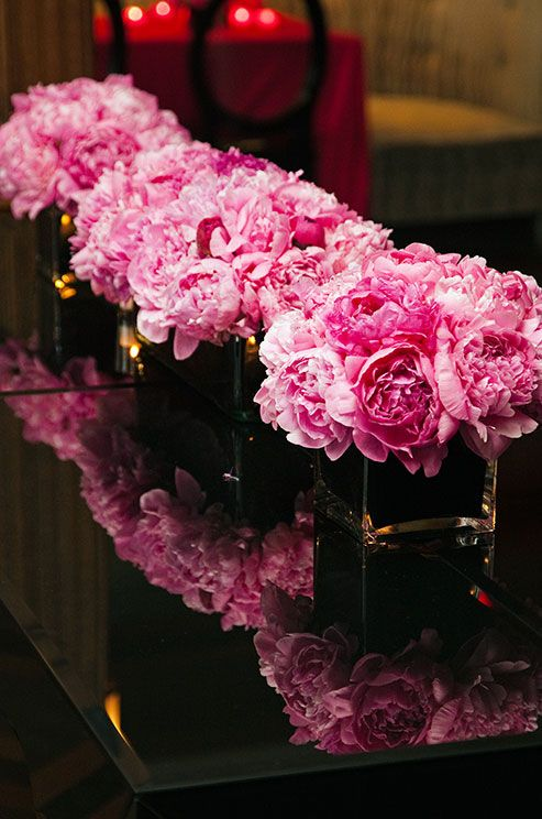 Pink peonies stand out among the dark décor that surrounds- fabulous for a reception lounge!