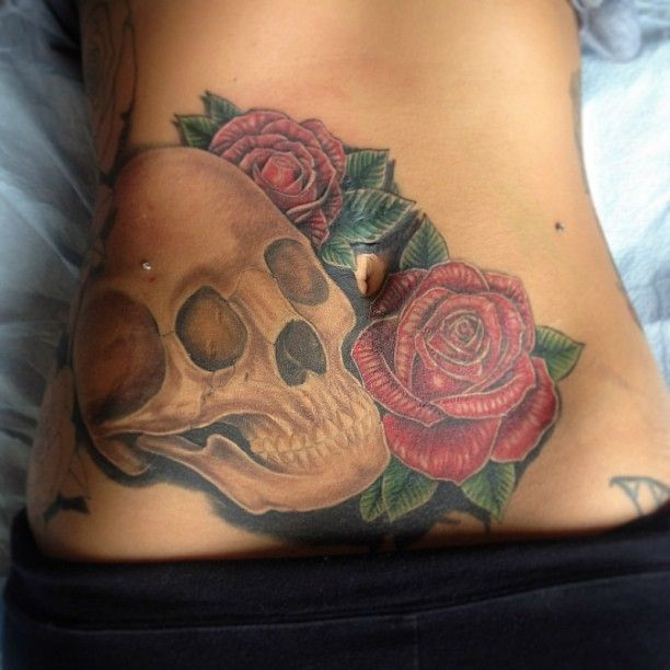 Skull and roses tattoo on the stomach