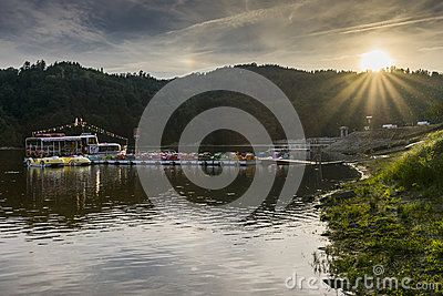 Small touristic ship name Rak moor to the platform on the Lake in Roznow , Poland. Europe. Sunset time .