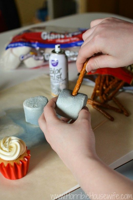 Adding a pretzel rod to the silver marshmallow to finish the Thor hammer cupcakes for my Mavel Avengers party