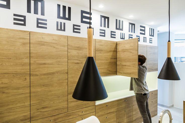 Diseño de interiores para óptica. Se usa la típica gráfica de optometría impresa en vinilo como elemento decorativo. Lámparas suspendidas en hierro lacado color negro. Mobiliario integrado.