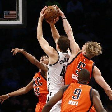 Oklahoma City Thunder frente Kyle Singler (5) e Trovão guarda Cameron Payne (22) defendem Brooklyn Nets guarda Bojan Bogdanovic (44) como Trovão frente Serge Ibaka (9) na primeira metade de um jogo de basquete da NBA, domingo, 24 de janeiro, 2016, em Nova York.  (AP Photo / Kathy Willens)
