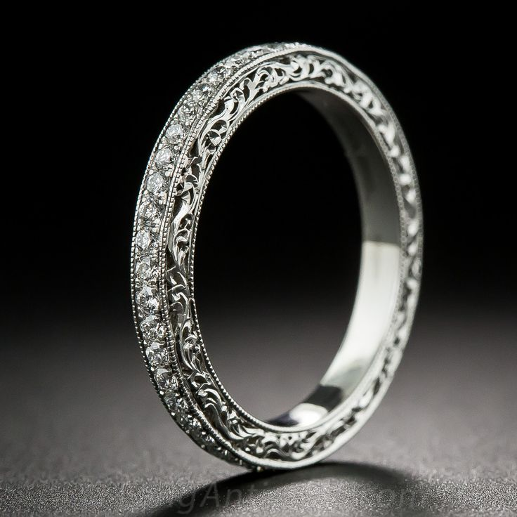 A finely crafted eternity band in platinum and ornamented with exquisite open scrollwork on the sides. Just over a half-carat of high-color, high-quality round brilliant-cut diamonds are bead set and bordered with a delicate milgrain edge. This band is a size 6 1/4, however it can be special ordered in your size. Please allow extra time for delivery. Price is subject to change.