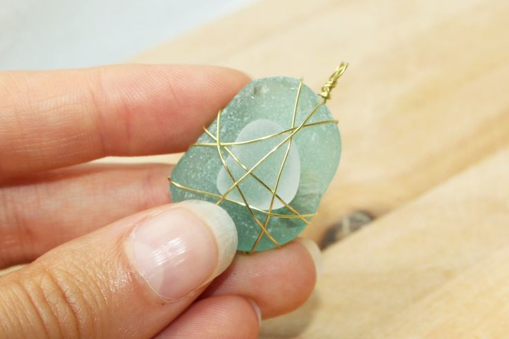 Wire wrapping sea glass for pendants.