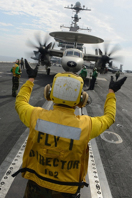A Sailor directs an E-2C at sea. by Official U.S. Navy Imagery