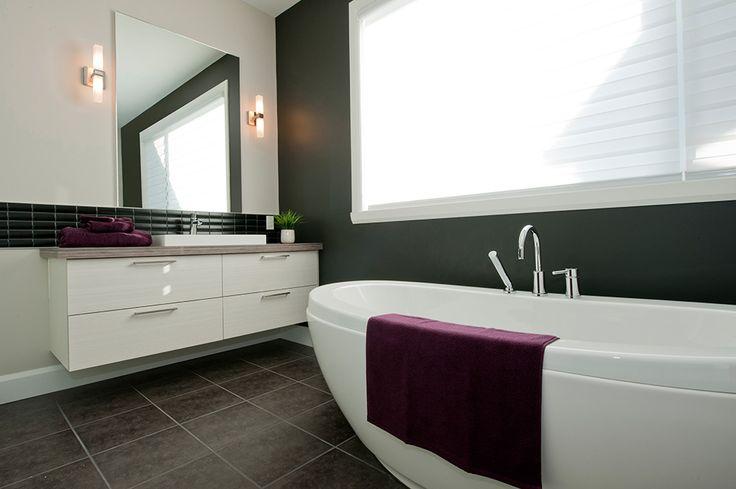 Très tendance, cette salle de bain et ses armoires de style panneaux plats en mélamine au grain horizontal allie rangement et fluidité de par sa vanité suspendue, les teintes des matériaux choisis et son comptoir de stratifié.