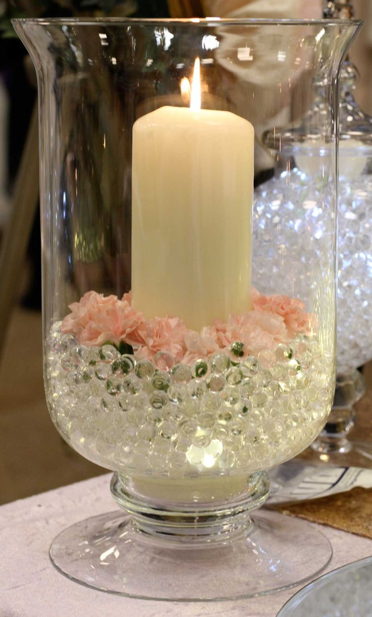 Large hurricane lamp decorated with pink carnations, gel balls and submersible lights, with a large pillar candle.