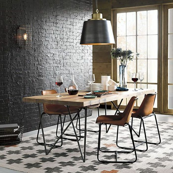 mur en briques noirs, lustre suspendu noir, table en bois brut, déco salle à manger
