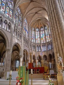 Basilica of St. Denis in Paris, France.  This church is said to be one of the first Gothic churches.  The architectural elements are pointed arches, high windows, and a prominent rose window.