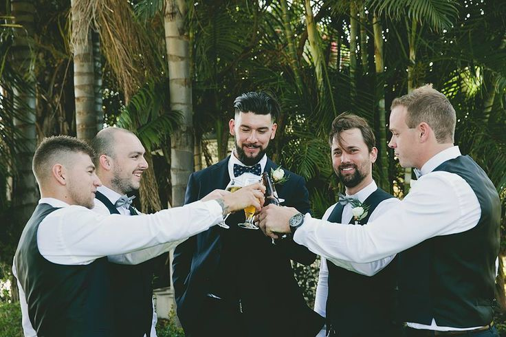 groomsmen and groom cheers on the day. Groomsmen wearing navy vests and grey bow ties. Groom in a blue bow tie and navy suit.