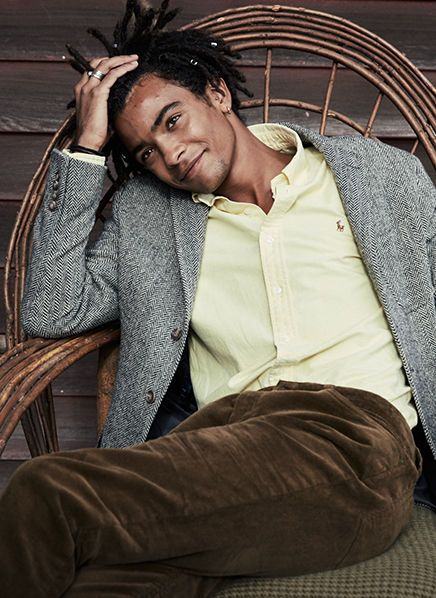 Man wears grey shawl cardigan, yellow shirt & brown corduroy pants