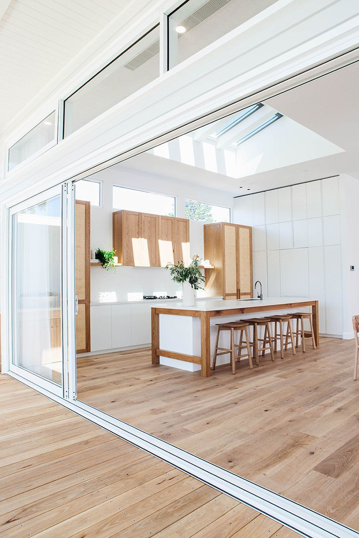 Modern White Kitchen With Matching Wood Flooring Inside And Out