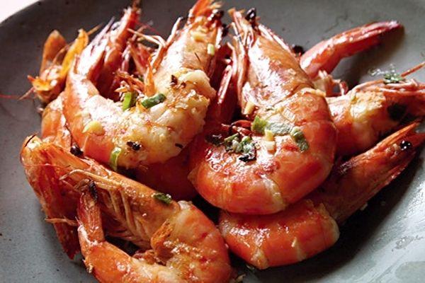Na rozpáleném másle a oleji osmahnuté plátky česneku, na něm opečené oloupané krevety.
