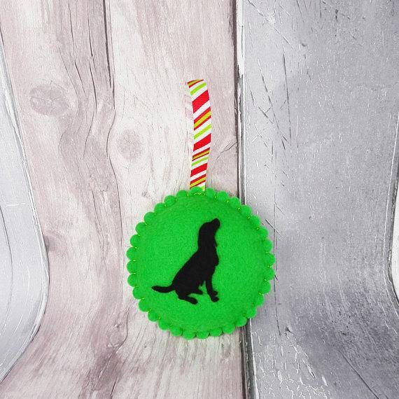 This beautiful handmade hanging felt ornament features the silhouette of a Spaniel and hand stitching around the edge of the decoration. This dog decoration is available in a variety of shades of green and red for you to choose from. This would be perfect to hang on a Christmas tree or anywhere around your home, especially if you are a dog fan, or as a gift for a dog lover.  Multiple decorations are included in the listing photos to show different colours and shapes available. The listing is…