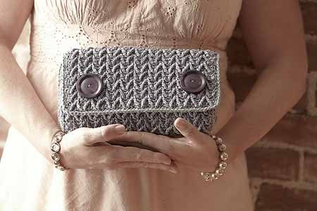 Go There Now Dropped double treble crochet stitches form this textured chevron pattern. A simple fabric lining hides the plastic canvas that gives this crochet clutch its sleek and sturdy shape. Magnetic snaps keep the flap in place, and large decorative buttons add modern style. Designed by: Brenda K. B. AndersonFinished Size: About 9 1/2″ …
