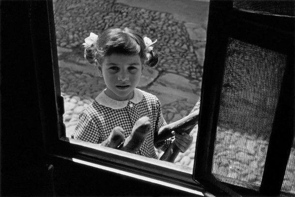 Young girl with breads, via Domenico Lo Monaco, Bagheria, Sicily, 1964, by Ferdinando Scianna