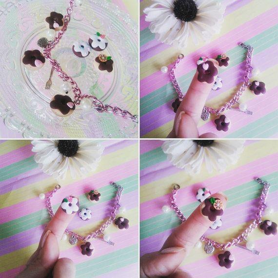 Delizioso braccialetto con ciambelline, perle ed altri abbellimenti. La catena di metallo è rosa, anallergica, lunga 18 cm+ chiusura ( in totale