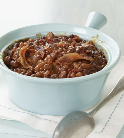Homemade crock pot baked beans with dried beans, molasses, mustard, brown sugar, ketchup, and other ingredients.