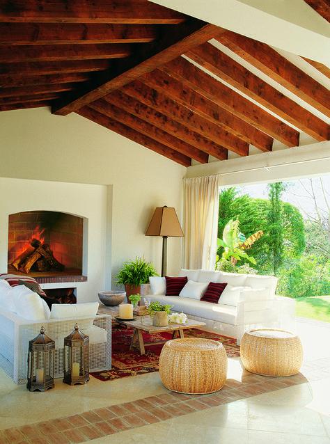 El estar del porche.Sofás diseñados por Pedro Peña, igual que la mesa de centro, de madera teñida y los pufs de ratán. Flores y plantas, en Viveros Martín.